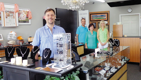 Photo by mike steely Jamie Smith stands at the counter of Karns Gold Smiths with his father, mother and wife behind him. The Karns store offers not only coins and jewelry but jewelry design.