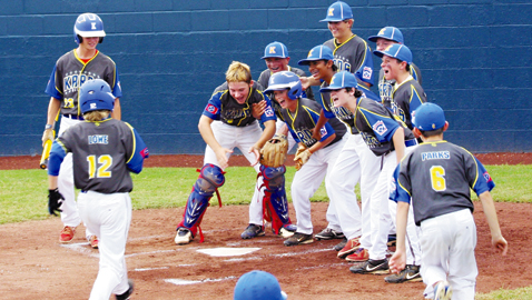 PHOTO BY CAROLYN GRENKOSKI Jubilant Karns teammates await for Mikey Lowe to touch home plate after he hit smacked a grand slam home run in a 15-5 win over Tullahoma in the State Little League tournament at Clarksville Thursday night.