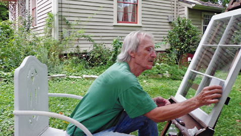 Barry Gregory restores a window at the Bethel Cemetery care-taker's home
