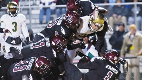 PHOTO BY JOHN VALENTINE A flock of Falcon defenders put the stop on a Catholic player in Fulton's 51-14 playoff victory Friday night at Bob Black Field.