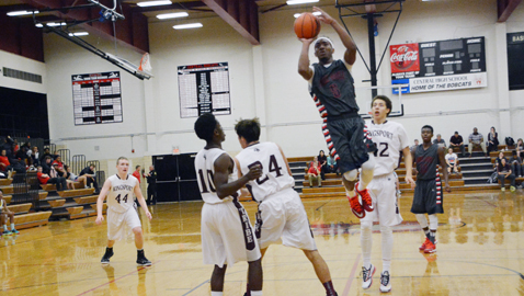 South-Doyle's Jarquese Goines leaps over Kingsport Dobyns-Bennett two Kingsport Dobyns-Bennett defenders to attempt a shot in a tournament game last Monday night. Goines scored 17 points in the Cherokees' 78-63 loss at Central High School. Photo by Dan Andrews.