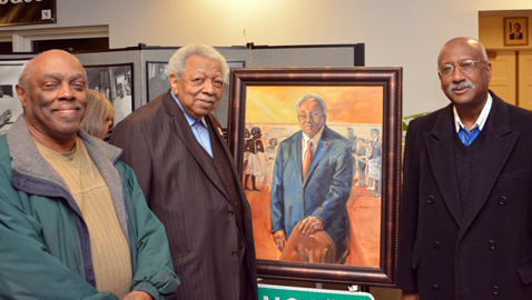 Photo by Dan Andrews. Dewey Roberts, Jr., Avon Rollins and commissioner Daniel Brown are pictured with a portrait of Rollins at the Beck Cultural Center.