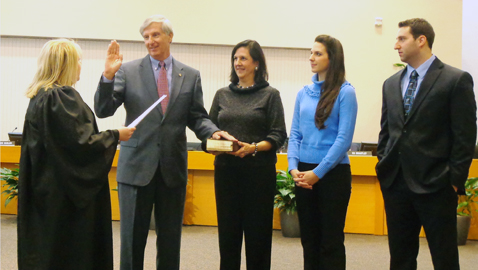 Newly appointed 5th District Commissioner John Schoonmaker takes the oath administered by Circuit Court Judge Kristi Davis as his family watches. His oath was taken just before the regular meeting of the commission last Monday. (Photo by Mike Steely)