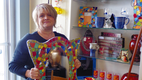 Photo by Mike Steely Jama Williams displays some of the locally made crafts inside Not Too Shabby Consignment. The store features clothing, furniture, jewelry, crafts, and much more.