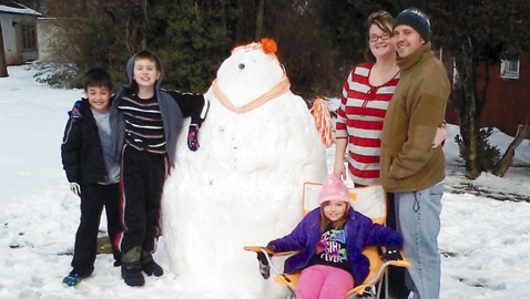 "PHOTO BY STEVE WILLIAMS ""Snowflake Volunteer"" was the creation of (from left) Zachariah Hunley, Jordan Taylor, Taylor Emert (in chair), Sabrina Welch and Jason Welch in the Inskip community following last Wednesday night's snowfall."