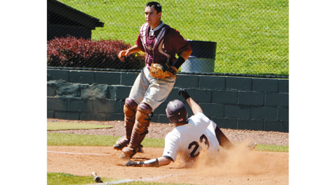 Photo by Dan Andrews. Bearden's Paul Underwood slides home past Oak Ridge catcher Chris Romannowski for the first run in the Bulldogs' 10-0 victory over the Wildcats Thursday afternoon at Farragut.