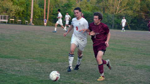 South-Doyle's Allen Kidd (9) battles with Morristown West's Matt Sawyer for the ball in the Trojans' 3-0 win over the Cherokees Wednesday night in the District 2-AAA Tournament. Sawyer scored the first goal of the match.