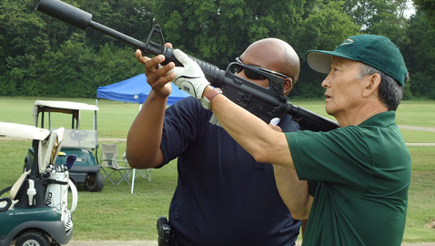 Dr. Kim tries out the rifle shot at his 2013 tournament.